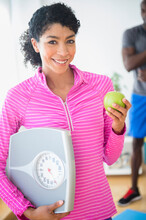 Woman Holding Apple And Scale In Gym