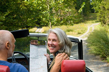 Older Couple Driving Convertible On Dirt Road