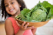 Mixed Race Girl Holding Bowl Of Vegetables