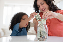 Mother And Daughter Saving Money In Jar