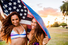 Women Standing Under American Flag Quilt At Sunset