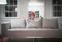Caucasian Boy Playing With Toy Sword In Living Room