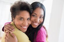 Black Women Hugging Cheek To Cheek
