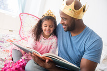 Father Ready Story To Daughter On Bed