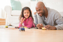 Father And Daughter Playing With Toy Cars On Floor