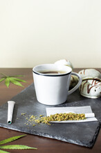 Fresh Coffee, Marijuana Leaves, Joints And Chocolate Donuts On Wooden Table With Copy Space Top.