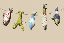 Decorative Set Of Textile Fish Hanging On A Rope. New Year's Gift For The Fisherman. Hand-made Crafts For The Holidays. Isolated On Sandy Background.