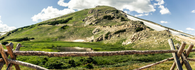 A wooden fence infront of small lake and rocky hill with remnants of snow in rocky moutains national park in america