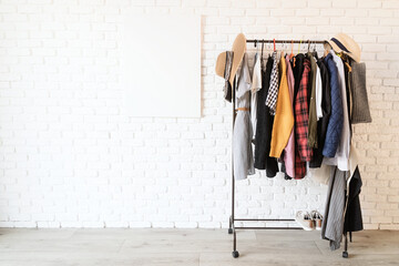 Rack with colorful clothes on hangers and frame canvas for mock up over white brick wall background