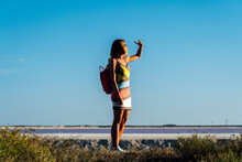 SIde View Of Stylish Middle Aged Traveller With Backpack Looking At Distance While Standing Near Pink Lake And Enjoying Sunset In Las Coloradas, Mexico