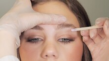 Correction Of A Shape Of Eyebrows With Hot Wax. Brow Master Applying Wax On The Eyebrow Of Female Face. Wax Correction Of The Shape Of The Eyebrows With Spatula. Beauty Industry. Close Up.