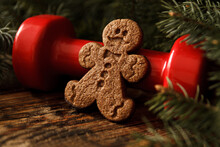 Delicious Gingerbread Man Cookie, Heavy Red Dumbbell And Christmas Tree Branches. Healthy Fitness Lifestyle Holiday Season Concept Composition, Cheat Day Temptation Vs Sticking To The Diet.