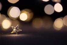 Guirnalda En Forma De Estrella Clavada Sobre Suelo Brillante Blanco Horizontal Con Fondo Desenfocado De Luces Doradas
