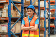 Leinwandbild Motiv Asian young happy female warehouse worker wearing safety vest and helmet at work in the industry storage warehouse. Portrait of female worker at warehouse. Inspection quality control