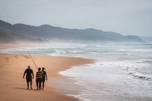 Three Fishermen Walking On The Indian Ocean Beach With Their Rods In A Foggy Day. KwaZulu-Natal, South Africa