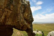 A Huge Rock Shaped Like An Elephant Against A Green Flied, Blue Sky And Clouds