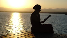 Silhouette Of Young Girl Reading Near The Sea