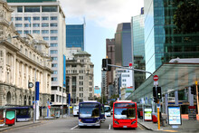 View Down Queen Street In The Cbd Or City Center Of Auckland, New Zealand. Shows Skyscrappers, And Historic Buildings As Well As Public Transport.