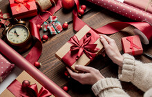 Woman Wrapping Gift On Wooden Table