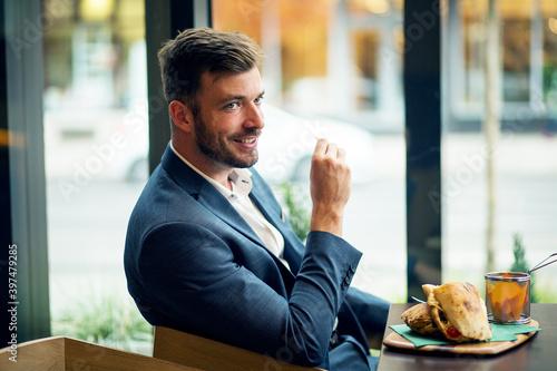 Fototapety, obrazy: Businessman eating food in restaurant