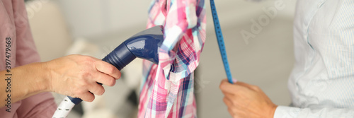 Shirt hangs on hanger it is steamed and measurements are taken with centimeter Fototapet