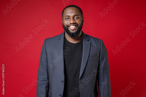 Smiling attractive confident successful young african american business man 20s wearing classic jacket suit standing and looking camera isolated on bright red color wall background studio portrait Fototapet