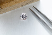 Macro Mineral Faceted Stone Morganite With Tweezers On A Gray Background