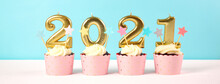 2021 Happy New Year's Eve Pastel Pink And Blue Theme Cupcakes With Large Gold Candles. Web Banner Sizing.