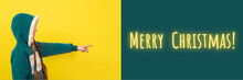 Teen Beautiful Girl Pointing Her Finger On Merry Christmas. Banner With Copy Space. New Year Or Christmas Concept