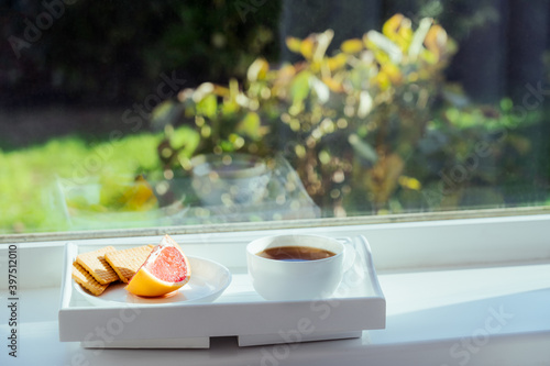 Cup of hot morning coffee, tea, grapefruit slice and cookies on the tray staying on the windowsill, indoors with green sunny garden background. Home Breakfast with a view. Selective focus, copy space.