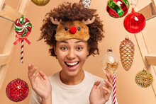 Festive Season Winter Holidays And Celebration Concept. Positive Dark Skinned Young Ethnic Woman Wears Reindeer Sleep Mask Raises Hands From Happiness Poses Against Decorated Christmas Background