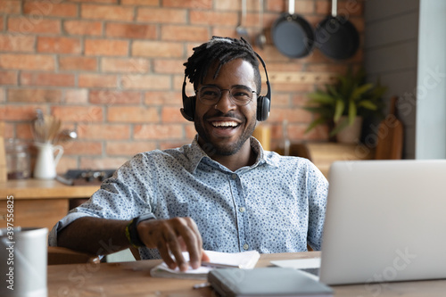 Fotografering Happy young african american man in eyewear and modern headset sitting at table with computer, laughing distracted from distant study or remote job, having fun entertaining feeling joyful at home