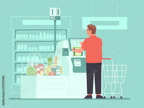 Fototapeta Self-service cashier in the supermarket. A man customer rings up groceries at a self-checkout terminals at a grocery store obraz