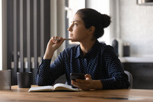 Pensive Young Hindu Female Study By Desk Using Mobile Internet Distracted From Making Notes Create New Idea. Thoughtful Mixed Race Woman Looking Aside Of Phone Screen Pondering Planning Future Work