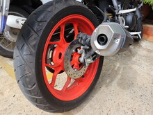 Close-up Of The Rear Wheel Of A Big Bike, Red Rims Modern Exhaust Pipe