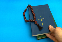 Reading Religious Literature And Freedom Of Religion. Take Bible With Christian Cross On Cover From Books Stack And Rosary Beads  Against Blue Background With Space For Text. Church Man. Copy Space