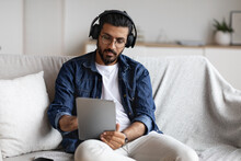 Indian Guy Spending Time At Home With Digital Tablet And Wireless Headphones