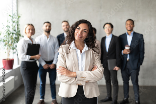 Businesswoman Standing In Front Of Her Employees Posing In Office