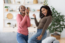 Carefree African American Girlfriends Singing And Dancing At Home