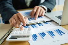 Asian Male Finance Businessmen Are Calculating Investment Results By Calculator, Company Performance From Graph Documents On The Desk In His Office, Business Ideas For Calculating Investment Results.