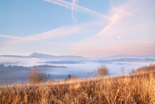 Sunrise In The Mountains, Pink Clouds And Full Moon, Autumn Pasture With Withered Grass, Deep Fog. Ukraine, Carpathians.