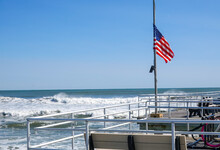 American Flag At Half Mast On A Wooden Boardwalk With Ocean Waves And A Clear Blue Cloudless Sky In The Background