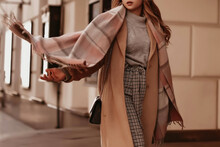Young Woman With Cropped Head In The Grey Knitted Cozy Sweater And Brown Coat Walking On The Street. Outdoor Portrait In Daylight. Warm Winter Clothes Concept