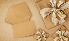 Greeting Gift Card, Top View Of Wrapped Packages Of Champagne Color With Golden Ribbon Bow, Envelope And Ticket, Isolated On Beige Background