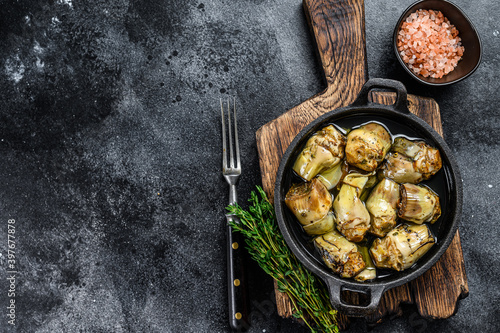 Fotografie, Obraz Canned artichokes in olive oil on a rustic wooden kitchen table