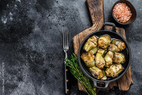 Billede på lærred Canned artichokes in olive oil on a rustic wooden kitchen table