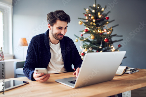 Fototapeta Cheerful man working from home with laptop and phone during Christmas obraz