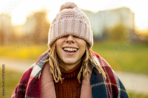 Fototapeta Cheerful woman covering eyes with knit hat while standing outdoors