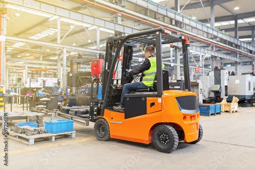 Fototapeta Storehouse employee in uniform working on forklift in modern automatic warehouse