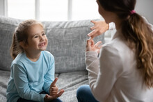 Smiling Cute Small Disabled Deaf Child Girl Learning Sign Language, Practicing Communication With Professional Therapist Or Mother At Home, Having Lesson With Teacher, Showing Symbols With Fingers.